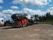 Red car carrier in Moncton hauling cars, vans, and a pickup truck