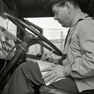Driver sitting inside a 1940s car carrier
